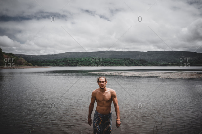 Attractive muscular man standing in calm river water on cloudy day in Galicia, Spain