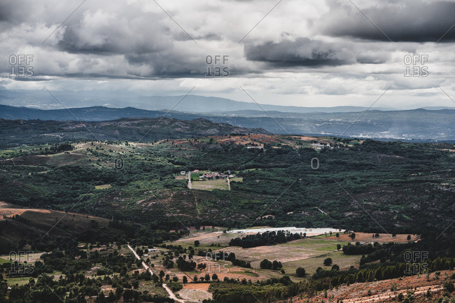 Drone view of thick clouds floating over beautiful green hills in Galicia, Spain