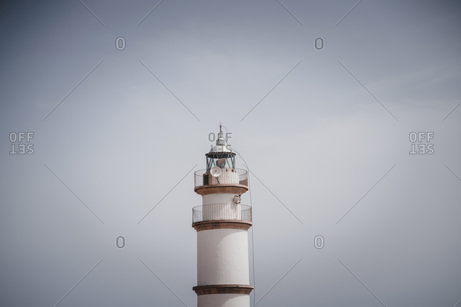 View of top of modern lighthouse on background of gray sky in Mallorca, Spain