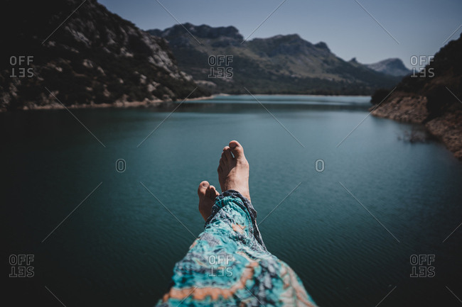 Legs of anonymous barefoot man on background of blue calm sea in Mallorca, Spain
