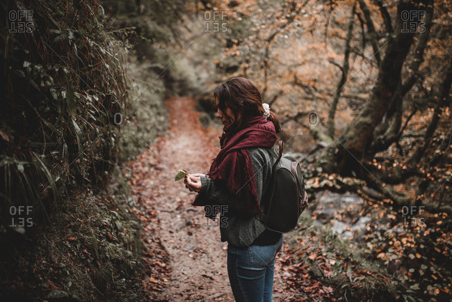 Side view of lovely young female in warm clothes holding leaf while standing on narrow path in autumn forest in Navarre, Spain