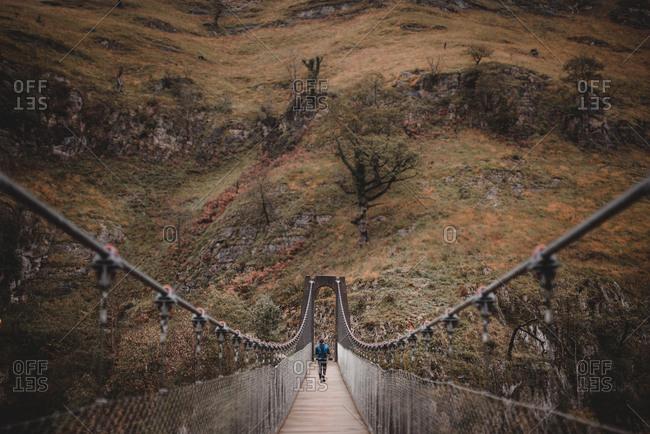 Anonymous person walking on hanging bridge