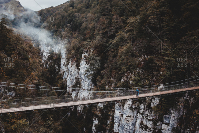 Breathtaking drone view of unrecognizable person standing on suspension bridge over magnificent canyon in Navarre, Spain
