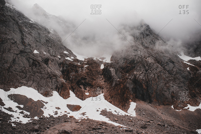 Murky mountains with snow in cloudy weather in Picos de Europa, Asturias, Spain