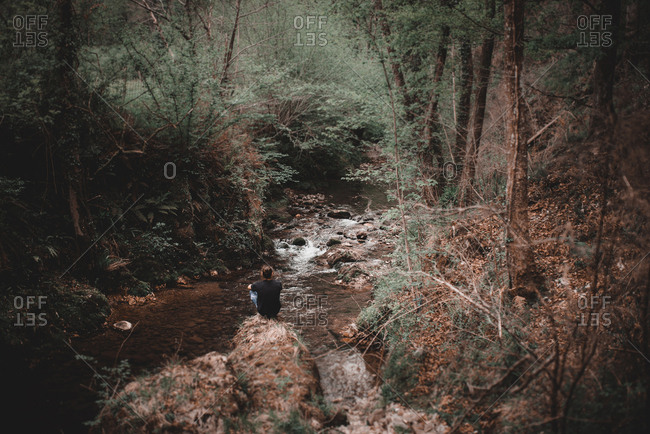 Man sitting on rock in mountain stream