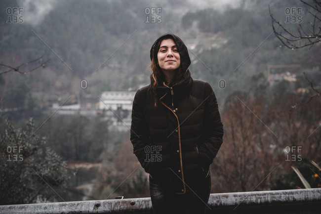 Lovely young lady in warm clothes smiling and looking at camera while standing on background of nature and settlement in Portugal
