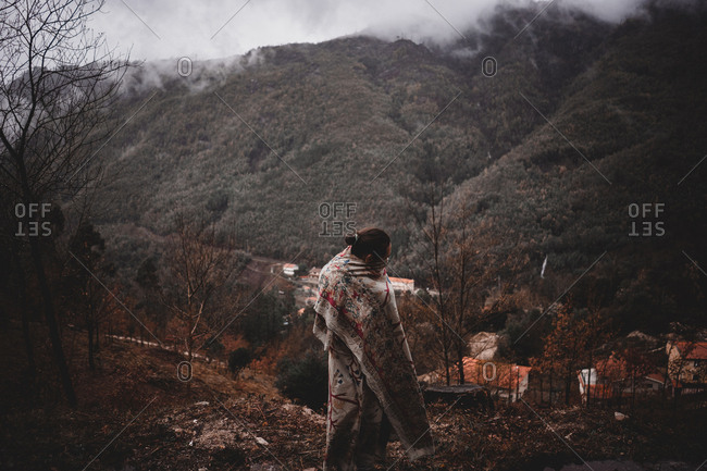 Man in blanket standing in countryside