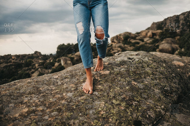 Crop shot of woman in stylish denim walking barefoot on rough gray boulder against cloudy sky