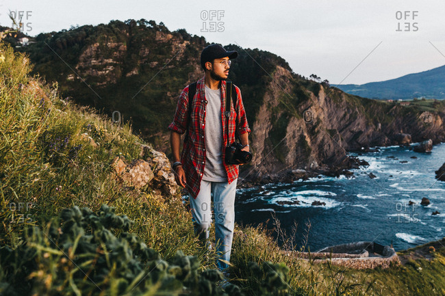 Handsome young guy with photo camera looking away while standing on cliff near water during trip in nature