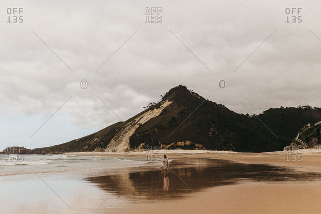 Unrecognizable person walking on wet sandy shore near sea water on background of mountain and cloudy sky