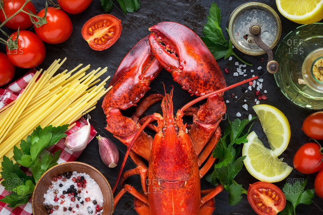 Steamed red lobster with spaghetti, red ripe cherry tomatoes, lemon wedges and parsley for cooking traditional Italian recipe Spaghetti all'astice