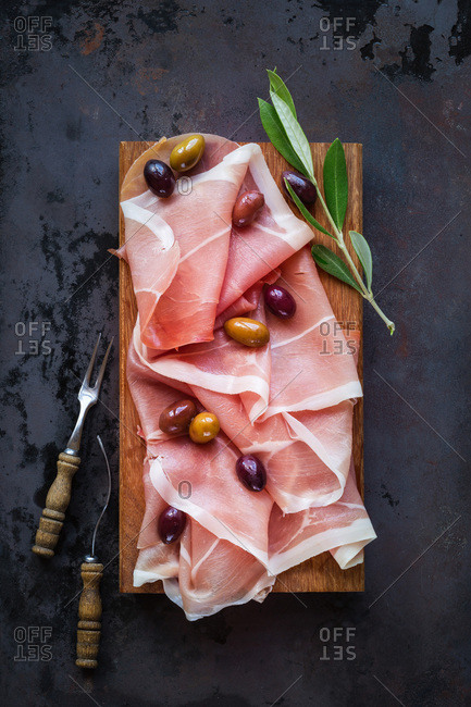 Prosciutto ham with olives on wooden cutting board