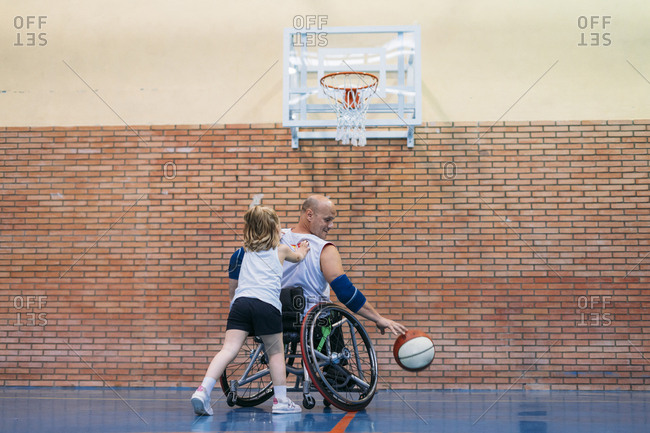 Disabled sport men and little girl in action while playing indoor basketball
