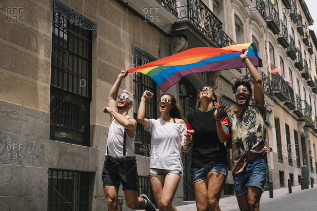 Group of friends with a flag of gay pride in the city of Madrid