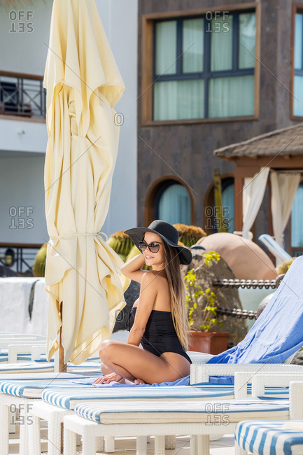 Side view of smiling sexy woman in swimsuit and sunglasses sitting on lounger