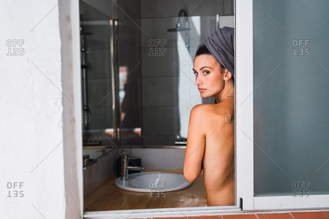 Young topless woman standing in bathroom