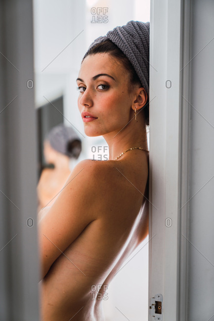 Young topless woman standing in front of mirror