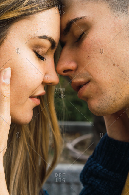 Side view of young loving people caressing each other and kissing with eyes closed.
