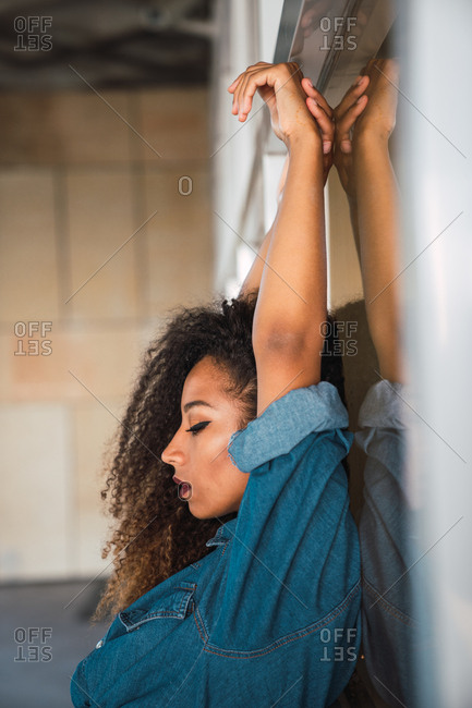 Side view of young African-American attractive woman with curly hair in denim shirt sitting near wall with hands up and closed eyes