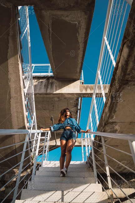 From below view of young African-American woman with dark hair in denim clothes going down on metal staircase on street at daylight