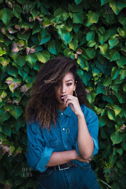 Young African-American woman with dark curly hair in denim clothes standing near tree with green foliage and looking at camera