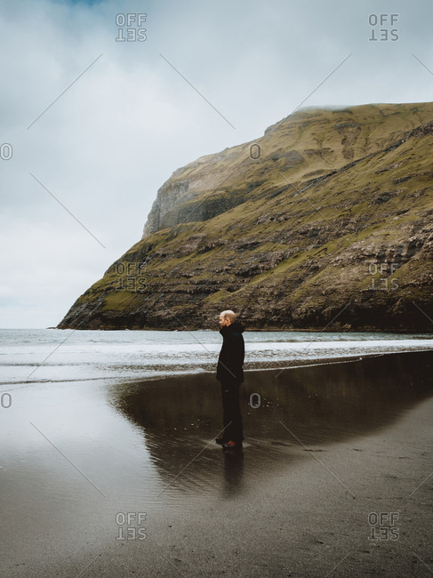 Side view of adult man in warm clothes standing on shore of calm ocean in Feroe Island