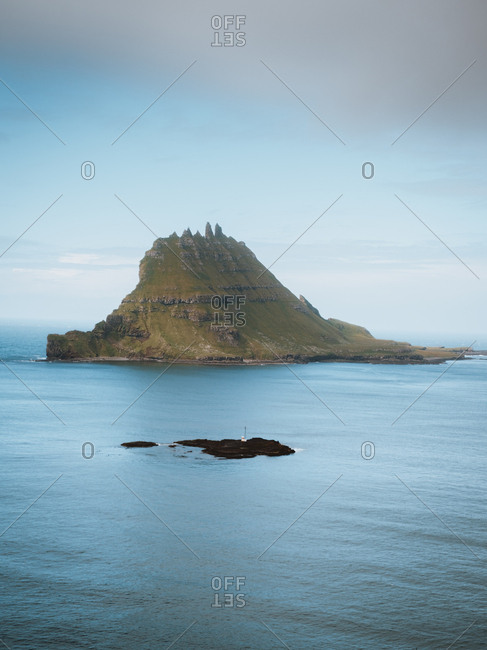 Picturesque view to calm blue ocean and small rocky Feroe Island