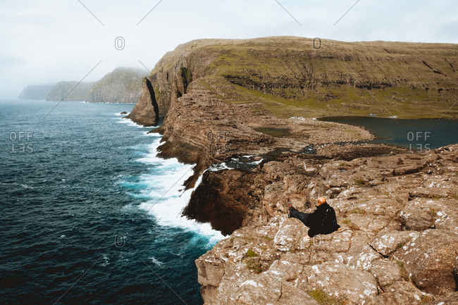 Hiker sitting and looking at ocean