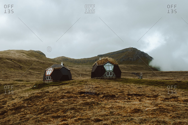 Two little contemporary houses on field with dry grass on hillside in Feroe Island