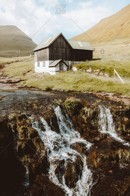 Small waterfall and wooden country house in hillside on Feroe Island