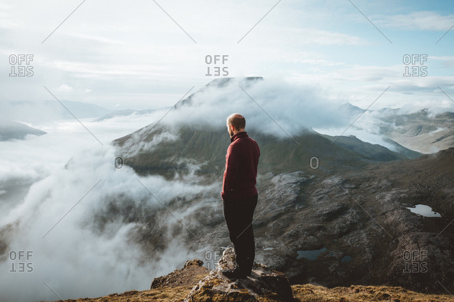 Back view of unrecognizable hiker standing on mountain edge on Feroe Island