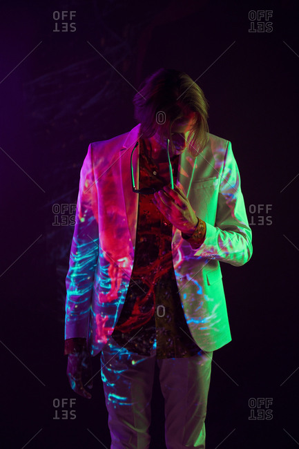 Androgynous male model in suit standing in relaxed pose under colorful illumination on black background