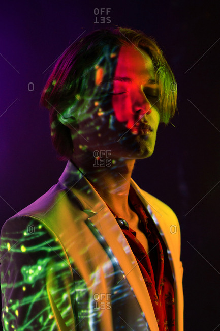 Attractive androgynous man keeping eyes closed while standing under colorful illumination in dark room