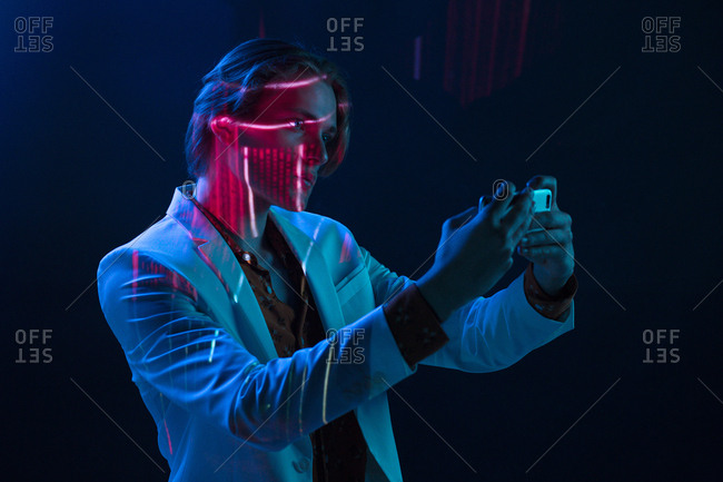 Abstract projection of face of attractive androgynous man in suit taking selfie in dark room