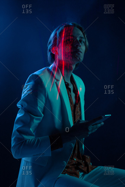 Abstract projection of face of attractive androgynous man in suit using smartphone in dark room