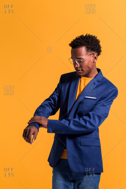 Stylish young black man wearing modern blue jacket with jeans and jumper standing on orange background