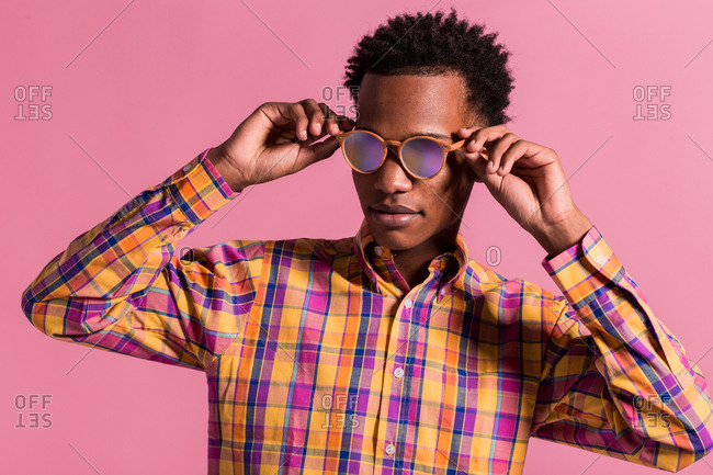 Trendy black man wearing colorful checkered shirt with shiny pink sunglasses standing on pink background