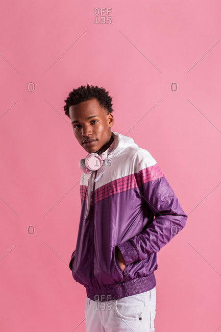 Young black man wearing modern trendy sportive jacket with headphones and looking at camera on pink background