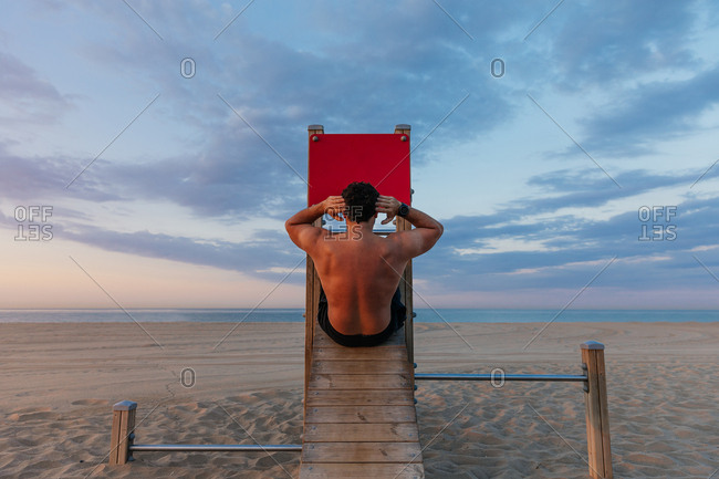 Back view of shirtless muscular guy doing abdominal crunches on wooden slide on beach