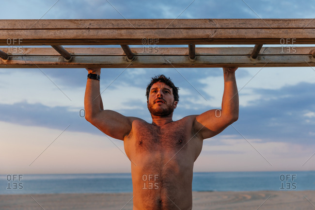 Bearded shirtless man climbing wooden horizontal ladder while exercising on beach