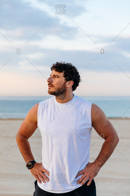Positive handsome man in sportswear keeping hands on waist while standing on sandy beach during sunset