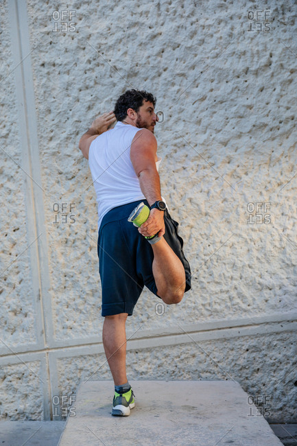 Back view of handsome adult man leaning on concrete wall and doing warming up exercise for legs during outdoor workout on street