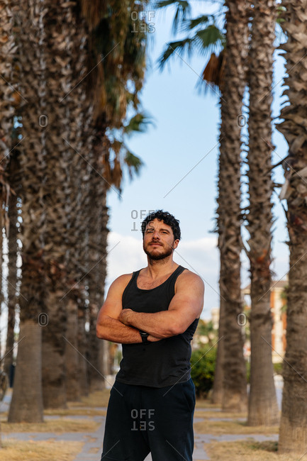 Handsome bearded man in sportswear keeping arms crossed and looking at camera while standing near tall palms during outdoor training