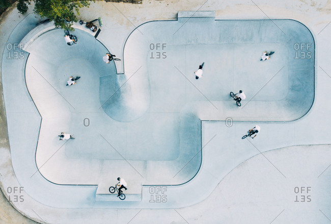 From above view of spacious skate park with group of men in white T-shirts doing tricks on BMX