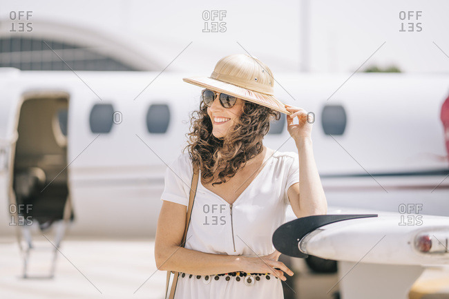 Pretty woman with sunglasses and hat next to an airplane.