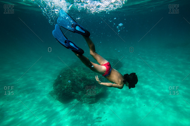 Anonymous boy snorkeling in sea