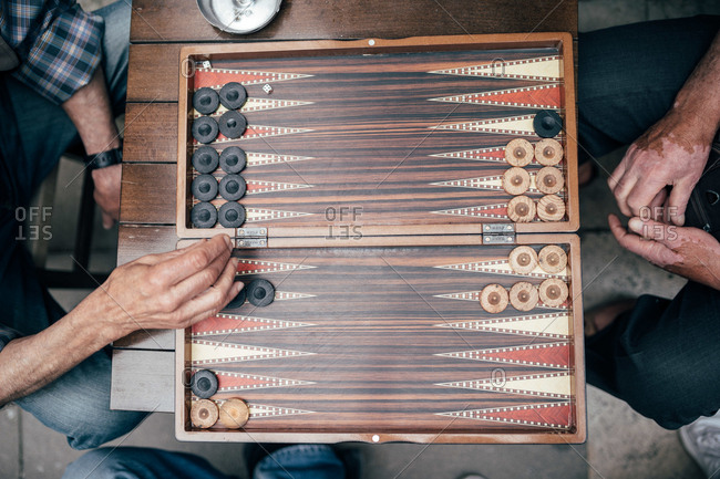 From above shot of two adult men playing backgammon while sitting on street of Istanbul