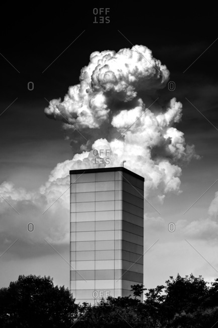 Black and white shot of thick cloud floating behind modern tower building in Istanbul, Turkey