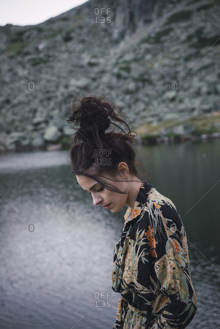 Young woman standing near rippling lake