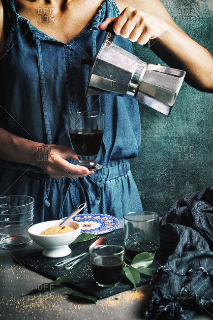 Woman serving coffee in crystal glass